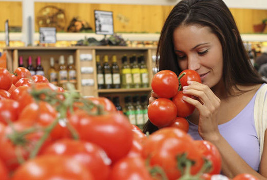 How to eat healthy on a budget, woman selecting tomatoes at the grocery store.