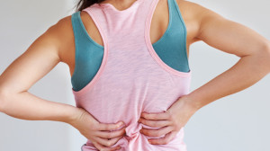 Beachbody Blog Muscle Soreness 5 Tips Woman Holding Back