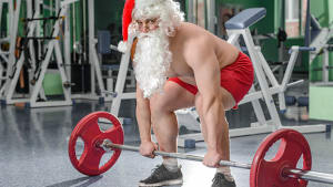 Santa Claus lifting weights in the gym