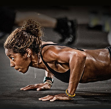 Photo of woman doing push-ups as part of the 22 Minute Hard Corps workout.