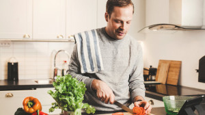 Man cutting fruits and vegetables for dinner organize kitchen for weight loss