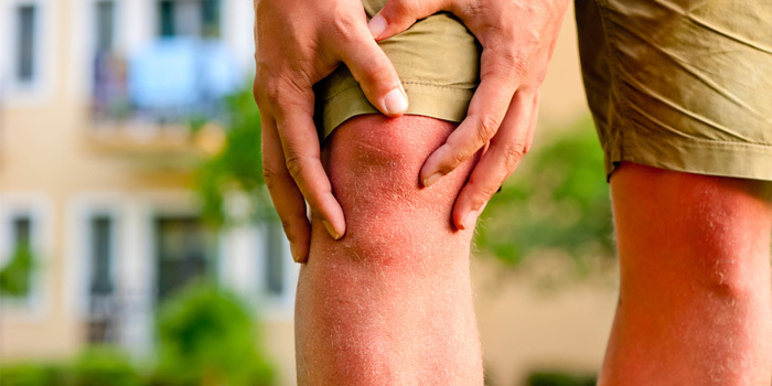 person with knee pain holding